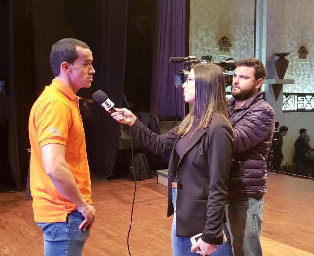 Eduarda Demeneck e Diogo Andrade, equipe da NSC TV em ação, durante entrevista com o percursionista Rodrigo Esteban Rúa Gómez, da Colômbia