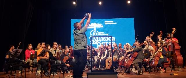 E quem disse que fotógrafo também não é um pouco maestro? A prova está aqui. André Arcênio, o fotógrafo oficial do Música na Serra, literalmente regendo com muita maestria essa imagem da orquestra!